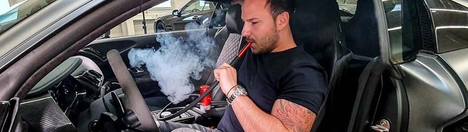 человек курит кальян в машине